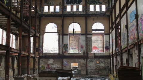 vidéos et rushes de slow upward pan of the graffitti covered walls of an abandoned building - délabré