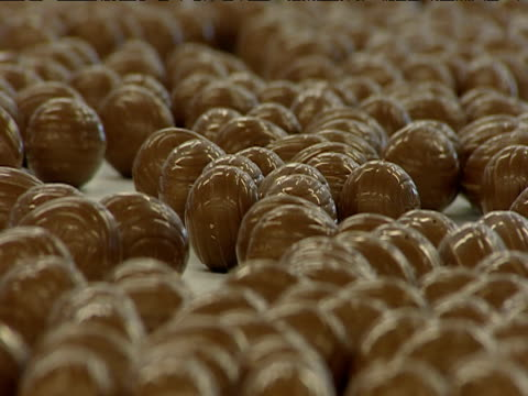 slow zoom as chocolate eggs wobble along factory conveyer belt - chocolate stock videos and b-roll footage