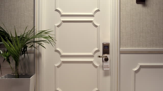 "slow zoom in on hotel door with ""do not disturb"" sign - hotelzimmer stock-videos und b-roll-filmmaterial"