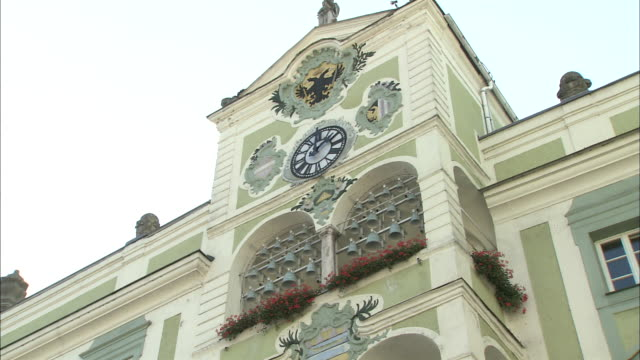 Slow zoom in to chiming carillon beneath clock on tower of town hall