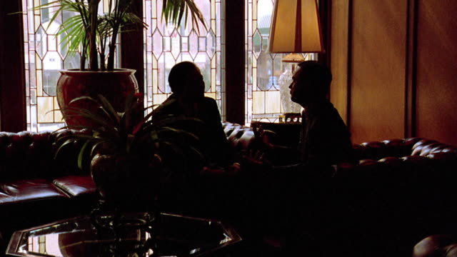 slow zoom in two silhouetted businessmen sitting on sofa talking in brown palace hotel lobby / denver, co - hotel stock videos & royalty-free footage