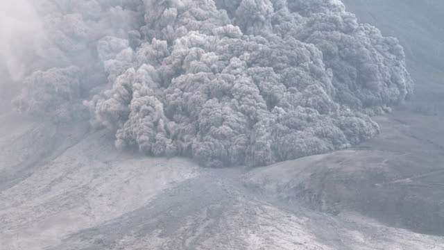 slow zoom on a large pyroclastic flow as it tears down the flanks of mt sinabung in indonesia during a powerful eruption - pyroklastischer strom stock-videos und b-roll-filmmaterial