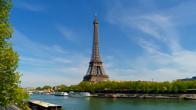 slow zoom out time-lapse of the eiffel tower and river seine, paris, france - eiffel tower paris stock videos & royalty-free footage