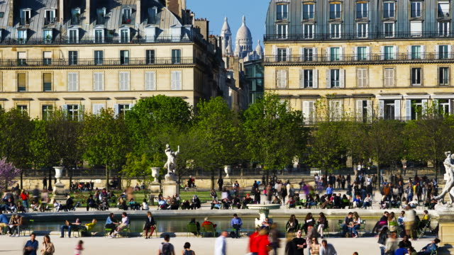 slow zoom out time-lapse of tourists at tuileries gardens with sacre couer in background - サクレクール大聖堂点の映像素材/bロール