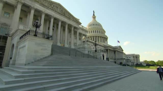 stockvideo's en b-roll-footage met slow zoom towards the center of the us capitol building as the american flag waves at half mast, a capitol police officer dominating a face mask... - zoom out