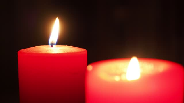 slowly burning flame of a red wax candle on an christian advent wreath - wreath stock videos & royalty-free footage