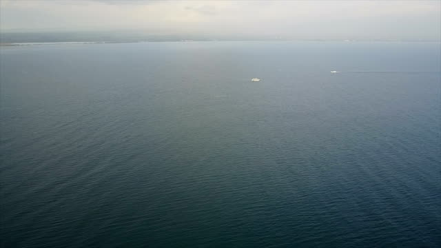 Slowly Flying Over Clam Ocean Under Stormy Sky off Maui Coast