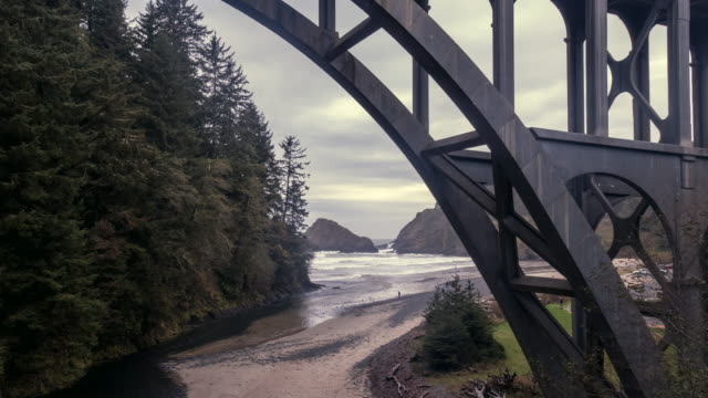 stockvideo's en b-roll-footage met slowly flying under cape creek bridge towards the beach - oregon coast