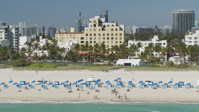 slowly panning drone shot of miami beach with miami skyline beyond - outdoor chair stock videos & royalty-free footage
