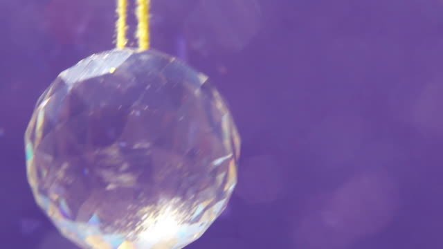 slowly rotating glass crystal pendant on purple background - pendant stock videos & royalty-free footage