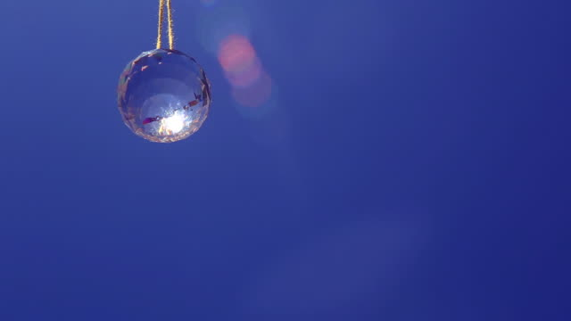 slowly rotating glass crystal pendant with blue sky and lens flare - pendant stock videos & royalty-free footage