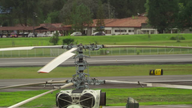 slowly turning helicopter rotors on airfield closeup - helicopter rotors stock videos and b-roll footage