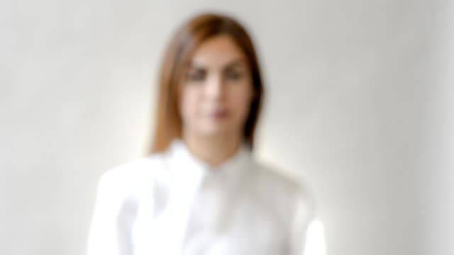 Slowly walking in to focus. Close up portrait of young modern middle east woman, looking straight in the camera. Shot with a tilt shift lens.