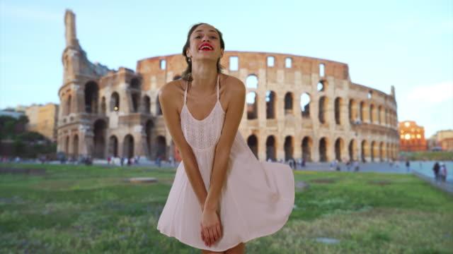 slowmo of beautiful latina woman in white sundress posing near roman colosseum - sundress stock videos & royalty-free footage