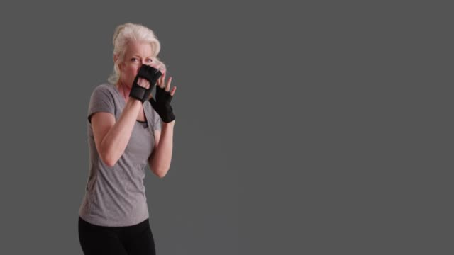 slowmo of energetic mature woman shadowboxing on grey background - art and craft stock videos & royalty-free footage