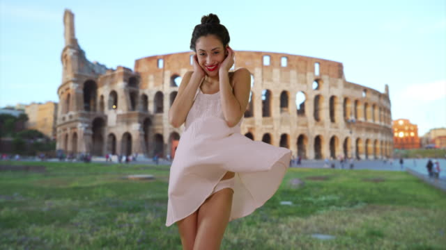 vídeos y material grabado en eventos de stock de slowmo of sexy latina female pushing dress down in the wind near roman coliseum - romano