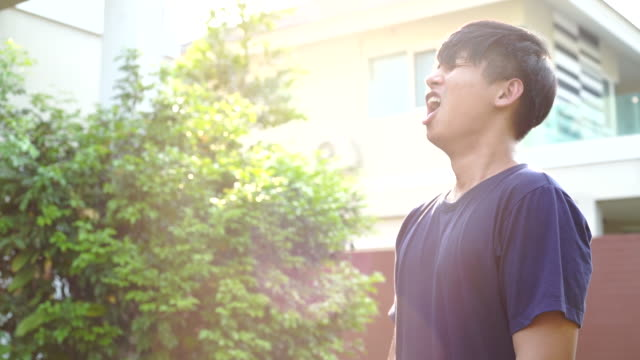 Slow-mo-Aufnahme von asiatischem Mann niesen zu Hause