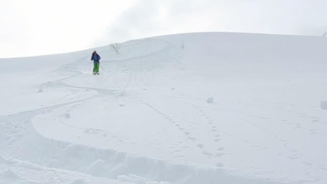 vídeos de stock e filmes b-roll de slow-mo view of skier descending, braking in deep snow - roupa de esqui