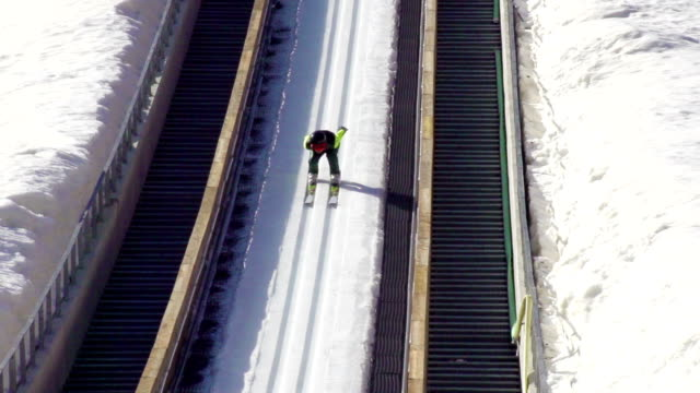 hd slow-mo: young man performing ski jump - ski jumping stock videos and b-roll footage