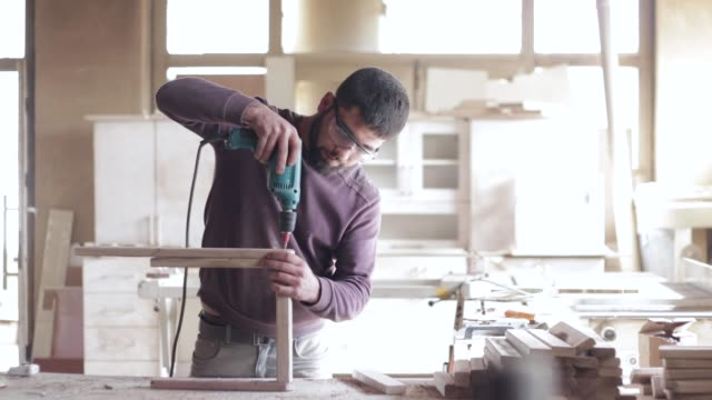 slow-mo-hand of worker drills a hole with wooden plank using electric drill machine in workshop - carpentry stock videos & royalty-free footage