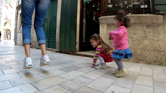 slow-mo-mother and her daughters jumping along the narrow street of the old town - old town stock videos & royalty-free footage