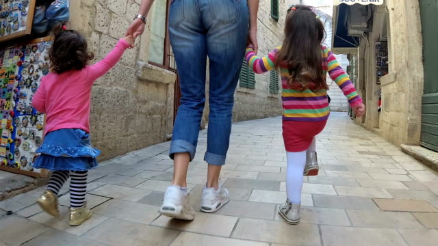 slow-mo-mother and her daughters jumping along the narrow street of the old town - narrow stock videos & royalty-free footage