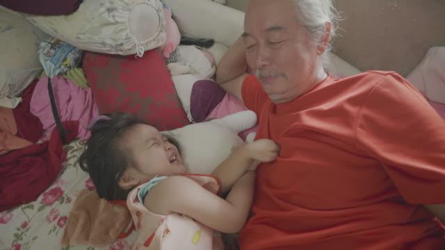 slow-motion asiatische baby mädchen verspielt mit großvater auf dem bett. - großeltern stock-videos und b-roll-filmmaterial