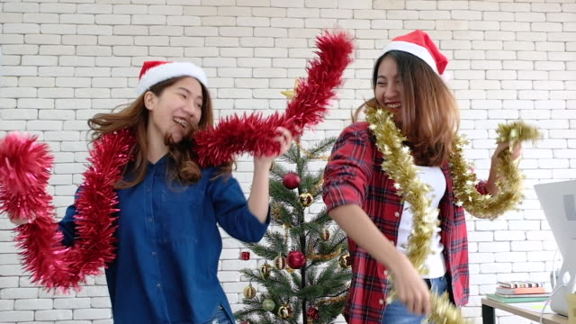 slowmotion asian female with tinsel and santa hat dancing in christmas party at office.xmas holiday celebration.creative office - tinsel stock videos & royalty-free footage