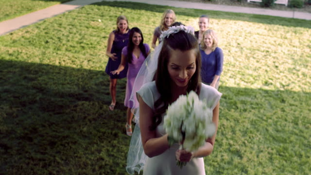 Slow-motion bride throwing bouquet of flowers.