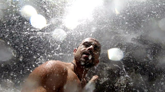 slowmotion clip of a man under a waterfall - taking a bath stock videos & royalty-free footage