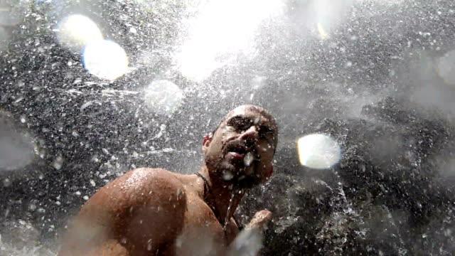 vidéos et rushes de clip de slowmotion d'un homme sous une chute d'eau - prendre un bain