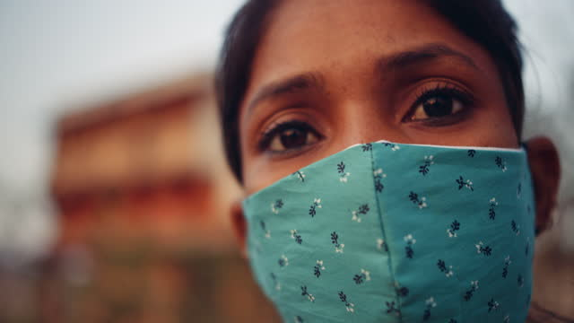 vidéos et rushes de slow-motion close-up of a young woman wearing fabric face mask as she gestures and points finger - indien d'inde