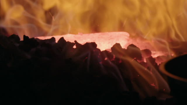 Slow-motion, close-up sequence showing metal being heated in hot coals in a blacksmithing workshop.