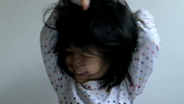 Slow-Motion closeup shot of a Chinese female toddler making faces