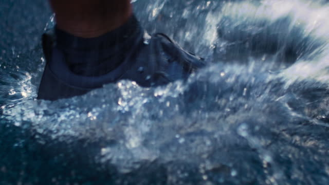 vídeos de stock e filmes b-roll de slow-motion close-up shot of a running shoe going through a puddle of water in the rain creating a splash - poça