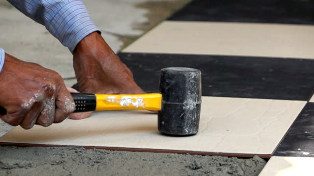 slow-motion, construction worker using hammer tiling floor - hammer stock videos and b-roll footage