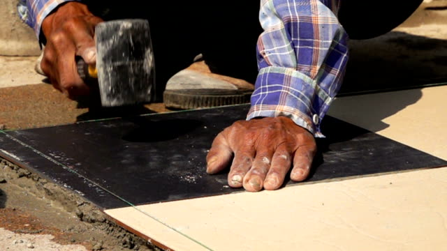 slow-motion, construction worker using hammer tiling floor