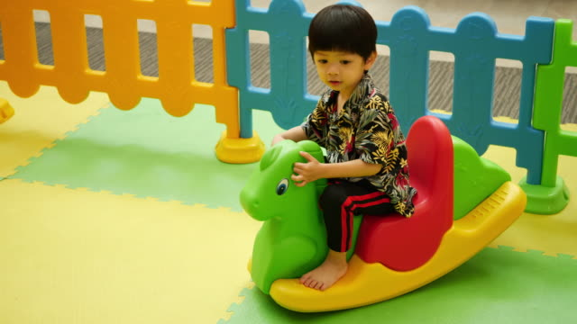slow-motion, cute boy playing toy in playground - indoors stock videos & royalty-free footage