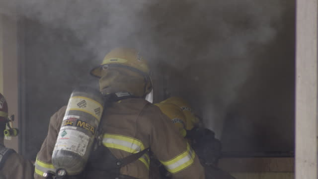 slow-motion firefighters spraying water through a window of a burning house - myrtle creek stock videos and b-roll footage