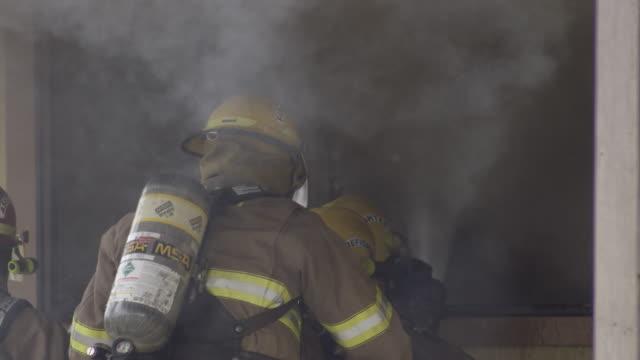 vídeos y material grabado en eventos de stock de slow-motion firefighters spraying water through a window of a burning house - parque de bomberos