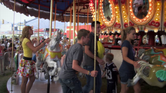 vidéos et rushes de slow-motion footage of four young adults walking up to carousel - couple d'adolescents
