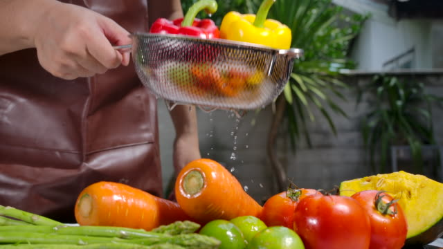 vídeos de stock e filmes b-roll de slow-motion he is washing fruits and vegetables. - pratos vegetarianos