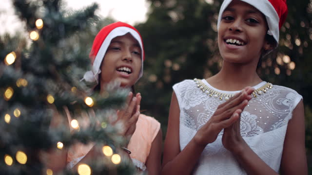 slow-motion medium shot of two sisters behind a decorated tree as the clap their hands sing christmas carols and wish everyone a merry holidays - christmas tree lighting ceremony stock videos & royalty-free footage