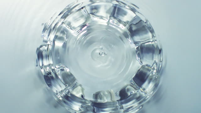 slowmotion movement of water drops and ripples with thirteeen submerged ice cubes in circle on light blue background - 余白点の映像素材/bロール