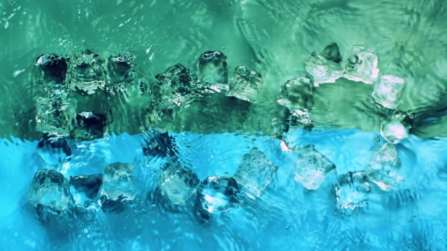 """slowmotion movement of waves and ripples on water surface with submerged ice cubes creating word """"eco"""", on light green background - single word stock videos & royalty-free footage"""