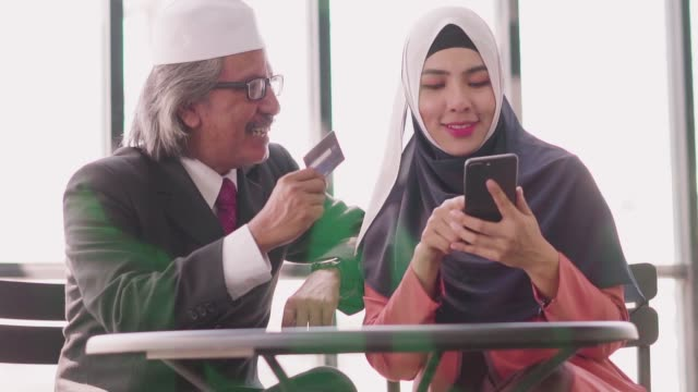slow-motion: muslim father and daughter shopping online with credit card and smartphone. - kufi stock videos & royalty-free footage