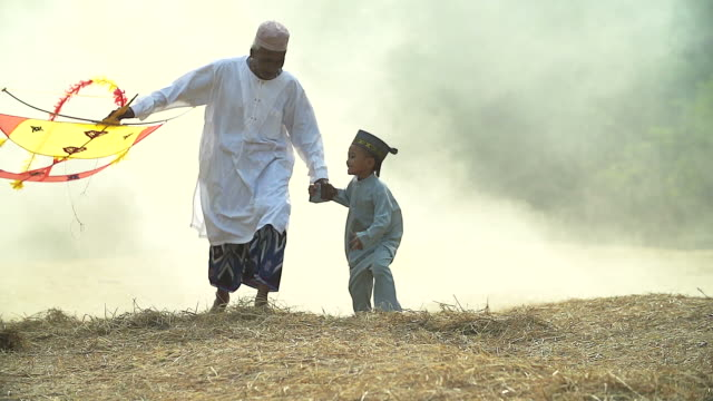 HD Slowmotion: Muslim grandfather and grandson flying a kite