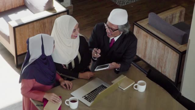 slow-motion: muslim people working and discussion with laptop in coffee shop. - kufi stock videos & royalty-free footage