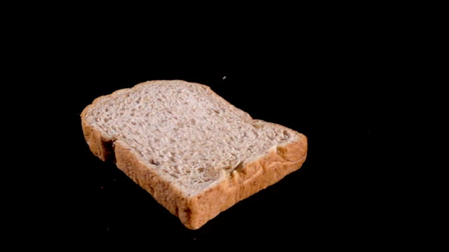 Slowmotion of bread drop on black floor