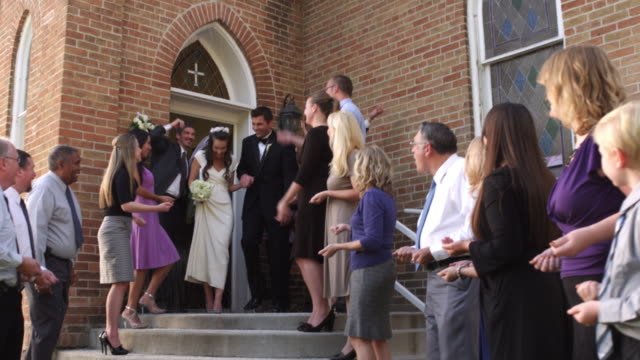 Slow-motion of guests throwing rice over a newlywed couple.